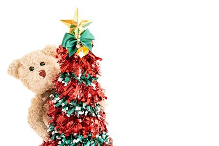 Christmas tree with a teddy bear and he play seek and hide happy feels in New year. Stock Photo