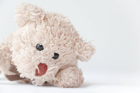 Cute little teddy bear lay down on the bed.