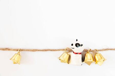 Golden bells on a brown rope and puppy with a white background, It is designed decoration for Christmas Stock Photo - 130129285
