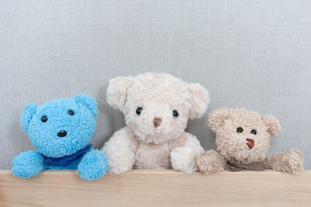 A gang of the teddy bears is catching on wood board on grey background