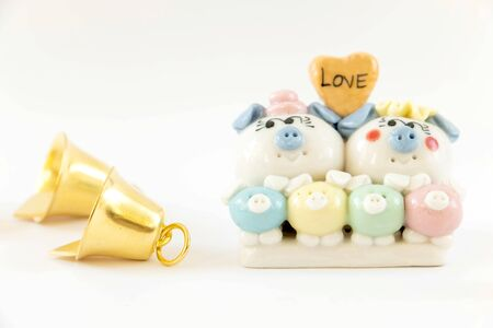 Golden bells and plaster pig family in love on a white background, It is designed decoration for Christmas