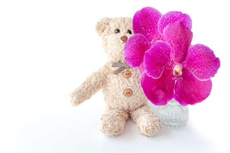 A cute teddy bear toy is sitting with fresh orchids in a glass vase.