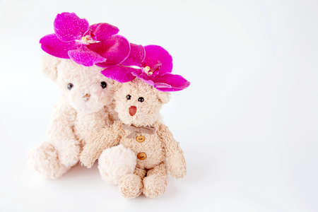 A cute couple of teddy bear toys is sitting with fresh orchids in a glass vase.