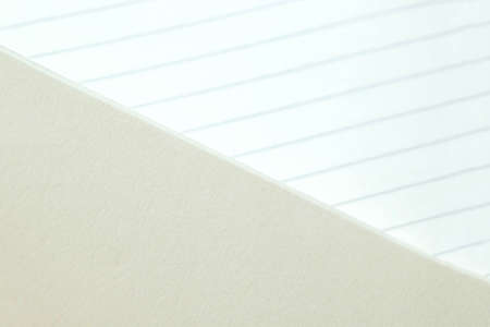 The texture of the paper background. Blank sheets of lined paper from a block on a gray background