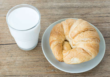 frence: A glass of milk with croissant on wooden background Stock Photo