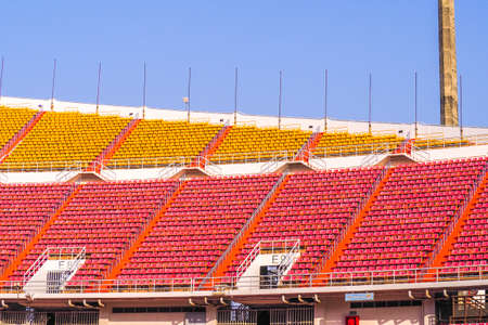 red and yellow Rows of empty seat in football stadium with blue sky background