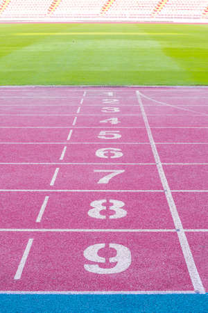 red running track field with number in the stadium background