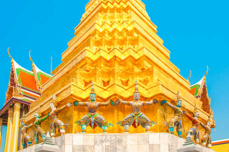 Giants under golden pagoda, Warrior statue with blue sky background at The Grand Palace and the temple Wat Phra Kaeo. Bangkok. Thailand, They are public domain or treasure of Buddhism.