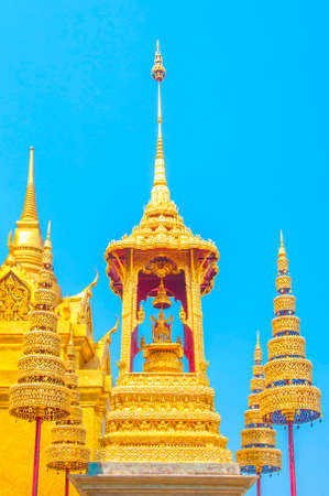 kaew: The Golden Crown and Throne with Pagoda, Temple and Blue Sky Background at Wat Phra Kaew, Grand Palace, Bangkok, Thailand.