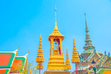 The Golden Crown and Throne with Temple and Blue Sky Background at Wat Phra Kaew, Grand Palace, Bangkok, Thailand. Stock Photo