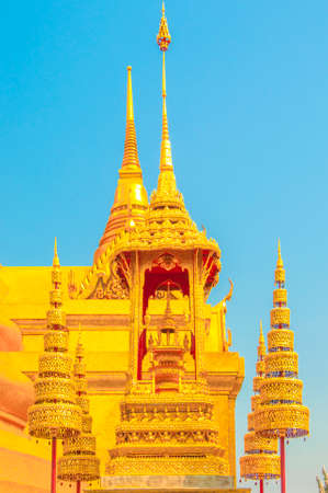 The Golden Crown and Throne with Pagoda, Temple and Blue Sky Background at Wat Phra Kaew, Grand Palace, Bangkok, Thailand.