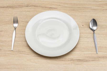 Close up impostazione del piatto bianco sul tavolo di legno. Concetto di pasto colazione.