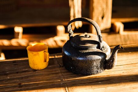houseware: Very old kettle on the table