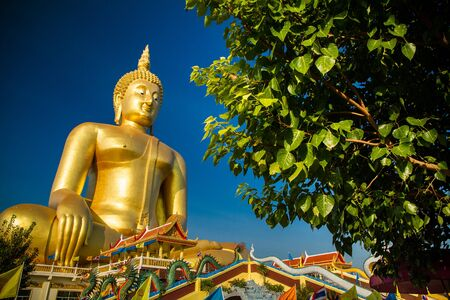 thai culture: The largest golden Buddha with blue sky as a backdrop. Stock Photo