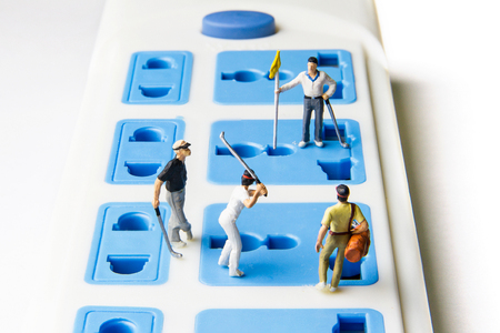 hit tech: Tiny toy golfers on the extension power strip Stock Photo