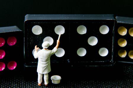 tiny: Tiny toy painter white on domino. Stock Photo