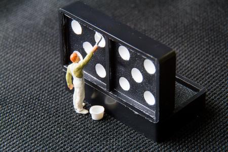 Tiny toy painter white on domino. Stock Photo