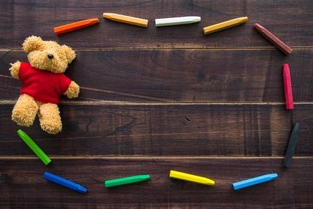 juguetes de madera: pasteles al óleo y la muñeca del oso pardo en la mesa de madera