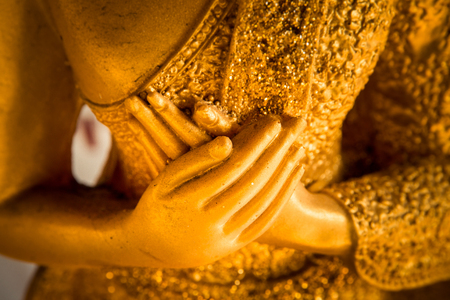 hands of buddha statue touching the heart on chest level.