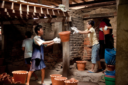 Workers carrying clay pots out of the kiln.Pak Kret.Nonthaburi, Thailand