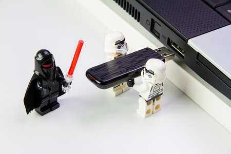 Nonthabure, Thailand - March, 19, 2016: Lego star wars stormtrooper plug the flash drive into notebook.The lego Star Wars mini figures from movie series on isolated white background, Lego is an interlocking brick system collected around the world by adult