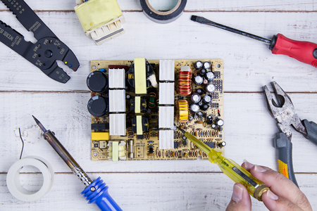 rosin: Serviceman check circuit board with electrical tester screwdriver in the service workshop. Stock Photo
