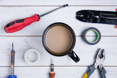 rosin: Coffee cup and equipment repair on the white wooden background.