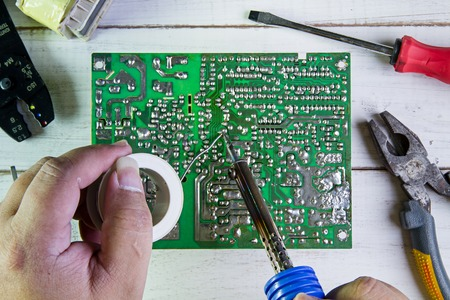 impedance: Serviceman soldering circuit board with soldering iron in the service workshop.