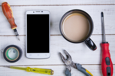 rosin: smartphone, coffee cup and equipment repair on the white wooden background. Stock Photo