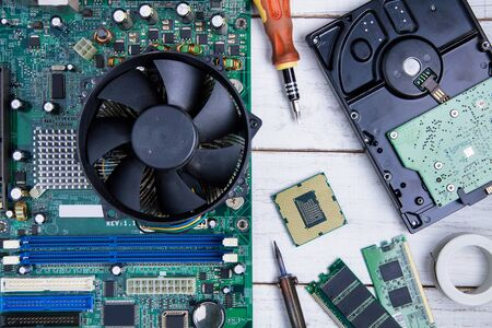 Computer motherboard, Computer Parts, Hard disk, Ram and equipment repair on the white wooden background. Фото со стока