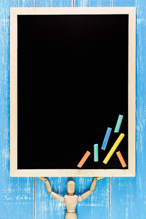 marioneta de madera: Wooden puppet is lifted Blank blackboard and color chalk on wooden table.Template mock up for adding your design and leave space beside frame for adding more text.