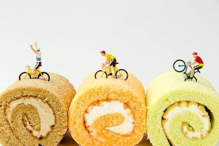 mini bike: Tiny toys ride bicycle on the jam roll cake,  paper sailboat.Food background Stock Photo