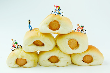 mini bike: Tiny toys ride a bicycle on the Sausage bread.Concept food background