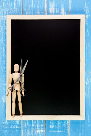 marioneta de madera: Blank blackboard and wooden puppet holding scissors hairdresser on wooden table.Template mock up for adding your design and leave space beside frame for adding more text. Foto de archivo