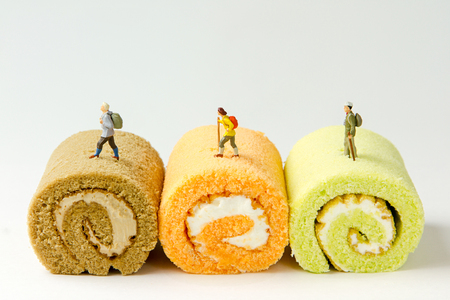 Tiny toys travelers adventure travel on the jam roll cake,  paper sailboat.Food background