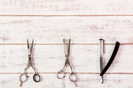 Scissors hairdresser and razor on wooden table.