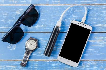 Slimme telefoon, zonnebril, draagbare batterij en kijk op blauwe houten achtergrond.