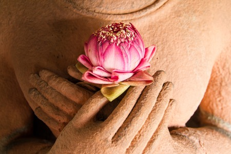 Lotus in the hands of sandstone Buddha. Stock Photo