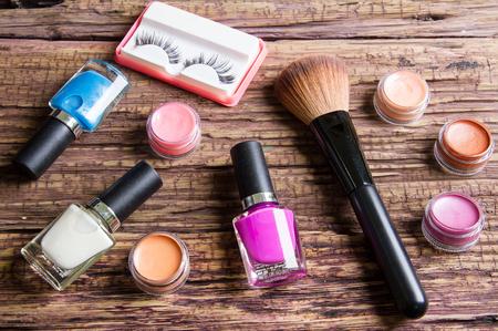 pestaÑas postizas: Grupo de pulimentos brillantes uñas, protector labial, pestañas postizas y cepillos para el maquillaje de madera de color marrón Foto de archivo