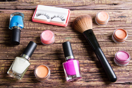 pestaÑas postizas: Group of bright nail polishes, lipstick balm, false eyelashes and brushes for makeup  on brown wood Foto de archivo