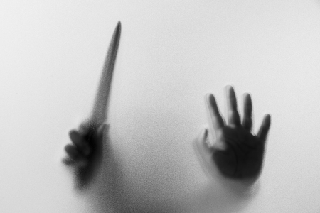 Shadow hands with knife of the Man behind frosted glass.Blurry hand abstraction.Halloween background.Black and white picture