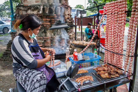 Ayutthaya, Thailand - October, 21, 2016 : Unidentified Thai woman is selling Isaan sausage, roasted pork and eggs grill at Wat Mahathat, Ayutthaya, Thailand