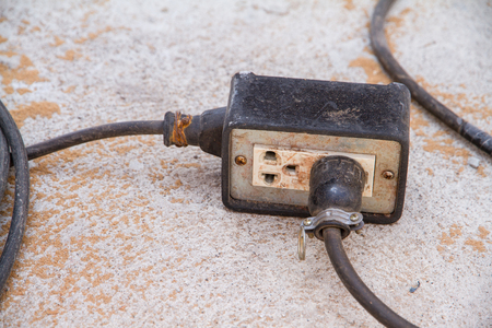 plugged in: Electrical socket with a cord or extension cord plugged in.