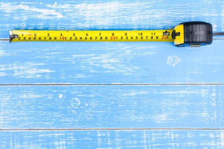 Tape measure on blue wooden table background copy space.maintenance concept.