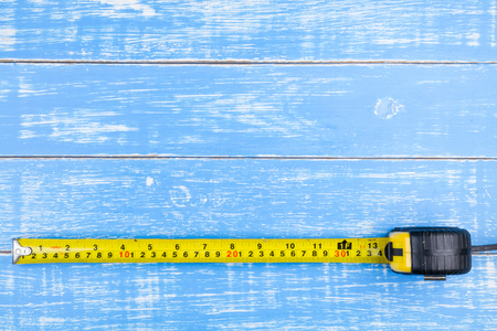 wooden metre: Tape measure on blue wooden table background copy space.maintenance concept.