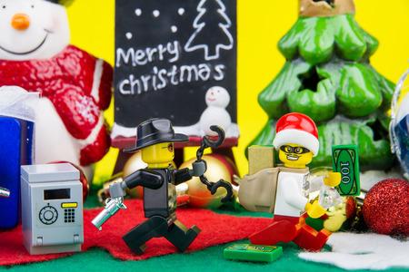 robo: Nonthaburi, Tailandia - noviembre 04, 2016: La policía de Lego Lego persiguiendo ladrón vestido como Santa Claus robó dinero y el oro en una caja fuerte en el fondo del día Christmas.Theme Navidad.