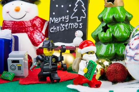 a white police motorcycle: Nonthaburi, Thailand - November, 04, 2016 : Lego Police chasing Lego thief dressed as Santa Claus stole money and gold in a safe at Christmas.Theme Christmas day background.