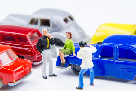 Miniature tiny toys photographer take photos man standing and woman sitting on car bonnet at the public car parking. Stock Photo
