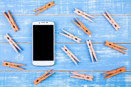 Orange wooden pegs on blue wooden background with smartphone and copy space.Template mock up for adding your design and copy space for adding more text.