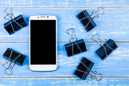 adding: Black Binder Clips on blue wooden background with smartphone and copy space .Template mock up for adding your design and copy space for adding more text.